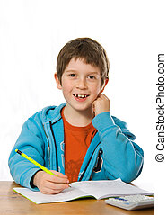 Boy doing homework - Happy young boy smiling whilst doing...