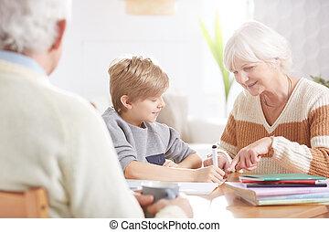 Boy doing homework with grandma