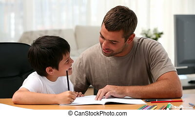 Boy doing homework with his father in the living room