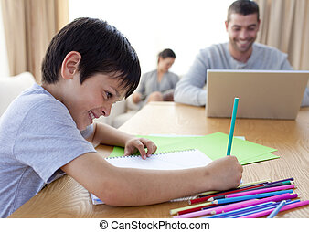 Boy drawing and parents working at home - Smiling boy...