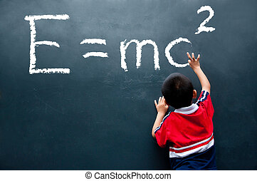 boy drawing E=mc2 on the wall