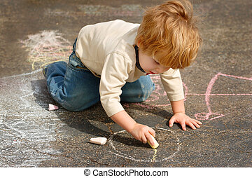 A young boy draws with chalk on a blacktop driveway