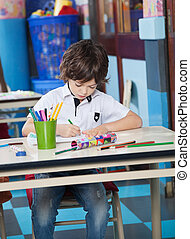 Boy Drawing With Student Sitting In Background