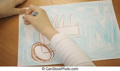 boy draws car wheels with pencil on paper