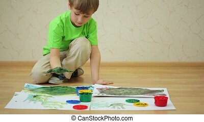 Boy draws color paints with his palm and fingers on sheet -...