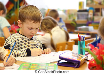 Boy draws in kindergarten