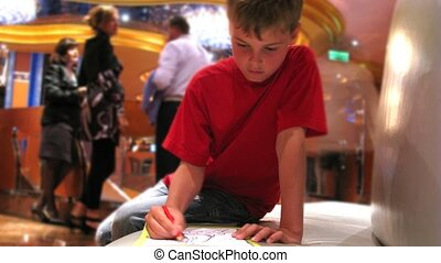 Boy draws something in front of bar rack