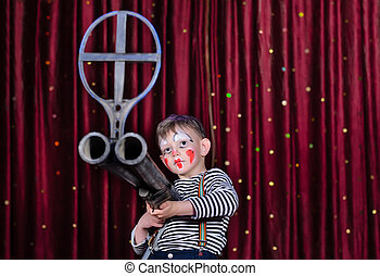 Boy Dressed As Clown Aiming Over Sized Rifle