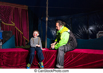 Boy Dressed as Clown Sitting on Stage with Man