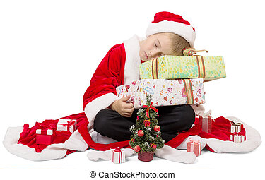 Boy dressed as Santa sleeping on Christmas gift
