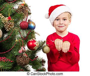 Boy dressed as Santa stands near a Christmas tree