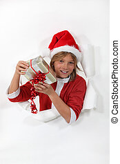 Boy dressed as Santa with a gift