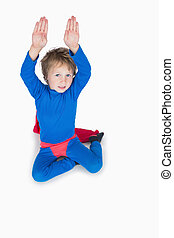 Boy dressed as superhero and raising arms