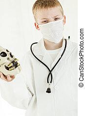 Boy dressed as surgeon holding plastic skull
