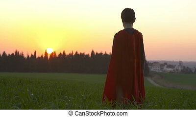 Boy dressed in a superman cape