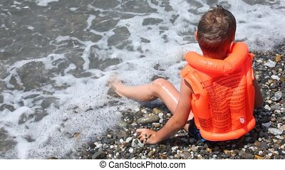 boy dressed in inflatable jacket sits on pebble beach and...