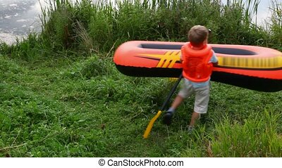 boy dressed in life jacket moving inflatable rubber
