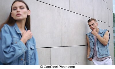 Boy dressed in pink shirt stands behind a seductive woman in jeans jacket