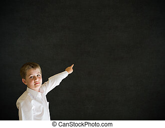 Boy dressed up as businessman pointing on blackboard background