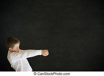 Boy dressed up as businessman pulling on blackboard background