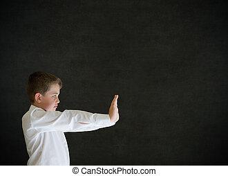 Boy dressed up as businessman pushing on blackboard background