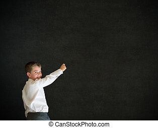 Boy dressed up as businessman writing on blackboard