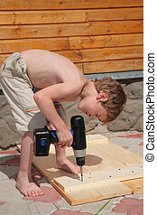 Boy drills with an electric drill