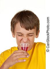 boy drinking medicine on white