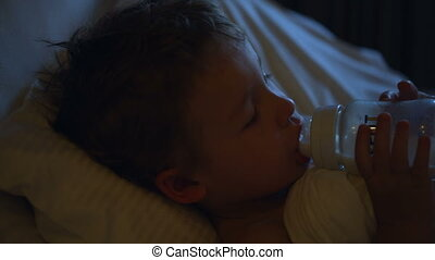 Boy drinking milk before bedtime - Close-up shot of a little...