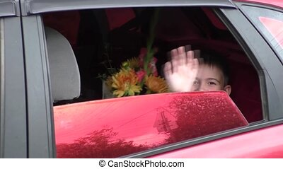 Boy drove by car - Boy with a bouquet of Orange dahlias and...