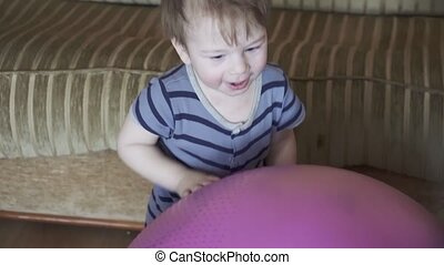 Boy drums on a fitness ball