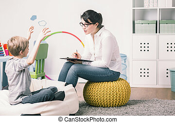 Excited boy and young teacher during private language lesson at home