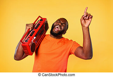 Boy ears the music with an old stereo and dances. emotional and energetic expression. yellow background