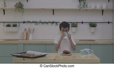 Boy eat cookie with milk. White Table in Kitchen. Cookies...