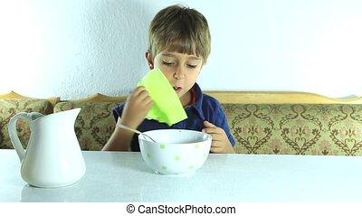 Boy eat granola with milk