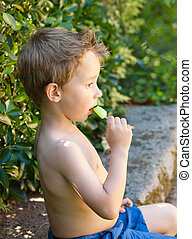 Boy eating an ice cream outdoors