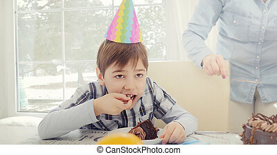 Boy eating birthday cake.