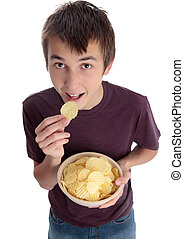 Boy eating chip snack and looking up