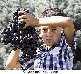 Boy eating grapes