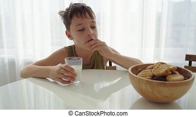 boy eating homemade cookies with milk at home kitchen