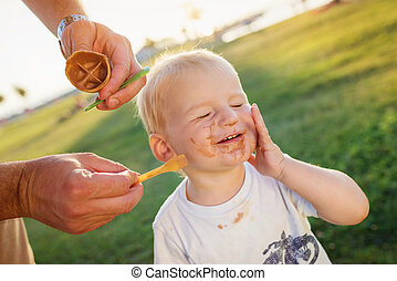 Boy eating ice cream, dirty face, green meadow, sunny