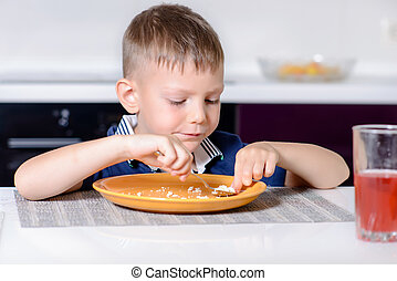 Boy Eating Last Bite of Food at Kitchen Table - Young Blond...