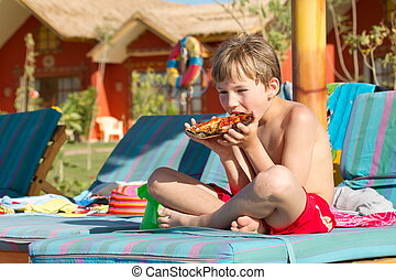 Boy eating pizza outdoors