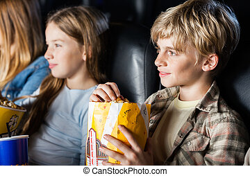 Boy Eating Popcorn While Watching Movie With Family