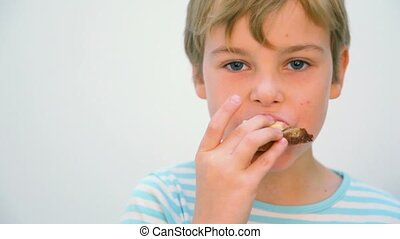 boy eating sandwich against white background