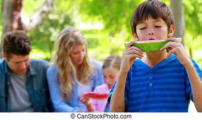 Boy eating watermelon with his family