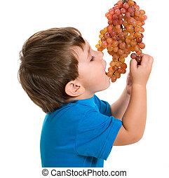 Boy eats a grape
