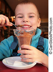 boy eats chocolate dessert