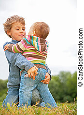 Boy embraces child on grass
