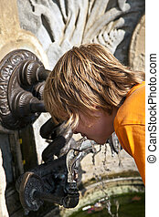 boy enjoys public trinking water - happy boy enjoys public...
